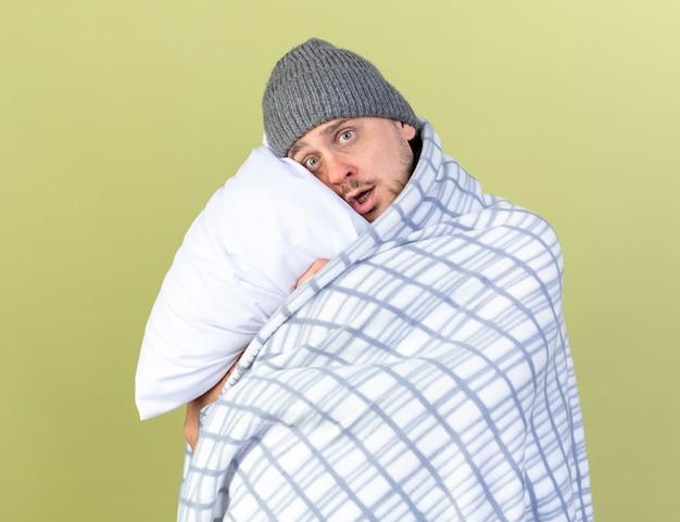Niespokojny młody blondyn chory ubrany w czapkę zimową owinięty w kratę przytula poduszkę na białym tle na oliwkowej ścianie