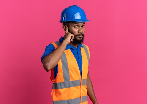 Niespokojny młody budowniczy mężczyzna w mundurze z hełmem ochronnym kładący palec na uchu odizolowany na różowej ścianie z miejscem na kopię
