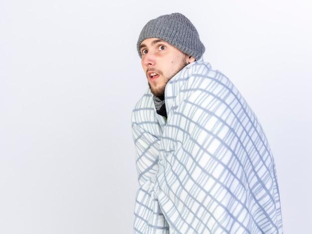 Niespokojny młody chory mężczyzna rasy kaukaskiej w czapce zimowej stoi bokiem owinięty w kratę