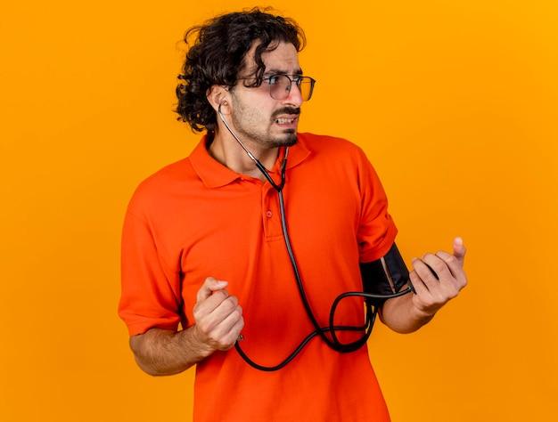 Niespokojny młody chory mężczyzna w okularach i stetoskopie mierzącym jego ciśnienie za pomocą ciśnieniomierza patrząc z boku odizolowanego na pomarańczowej ścianie