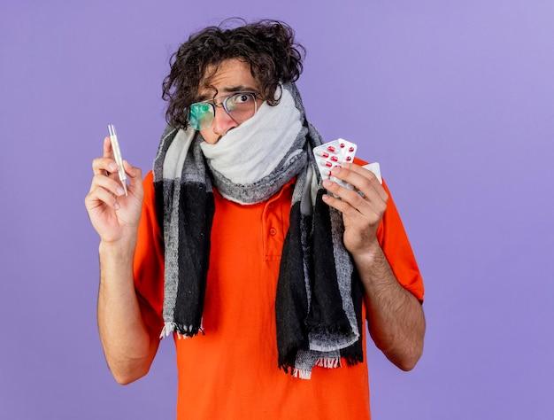 Niespokojny młody chory mężczyzna w okularach i szaliku trzymającym pigułki medyczne i termometr patrząc z przodu na białym tle na fioletowej ścianie z miejscem na kopię