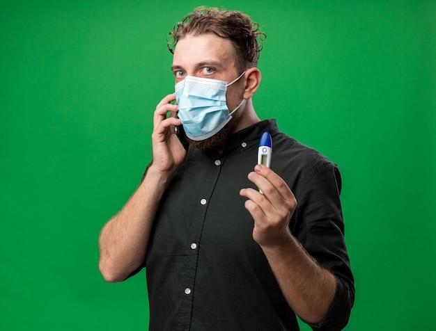 Niespokojny młody chory słowiański mężczyzna noszący maskę medyczną rozmawiający przez telefon i trzymający termometr