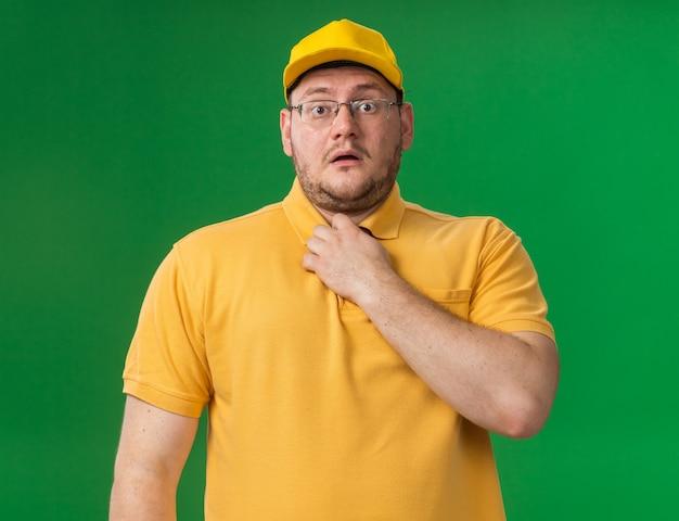 Niespokojny młody doręczyciel z nadwagą w okularach optycznych trzymający kołnierz odizolowany na zielonej ścianie z miejscem na kopię