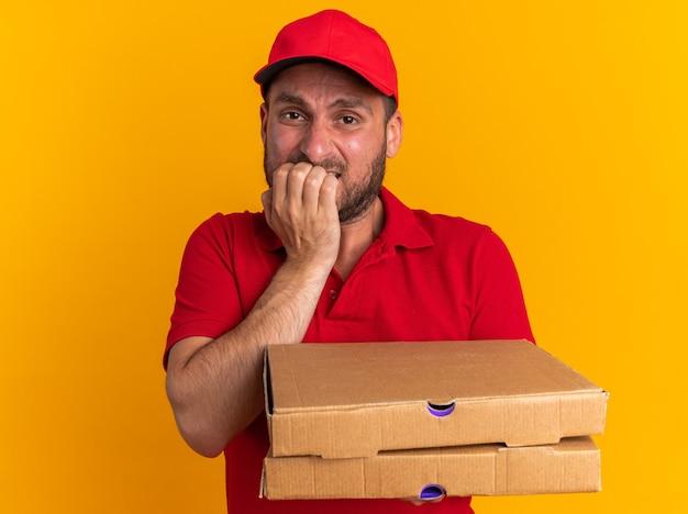 Niespokojny młody kaukaski dostawca w czerwonym mundurze i czapce, trzymający paczki z pizzą, gryzący palce