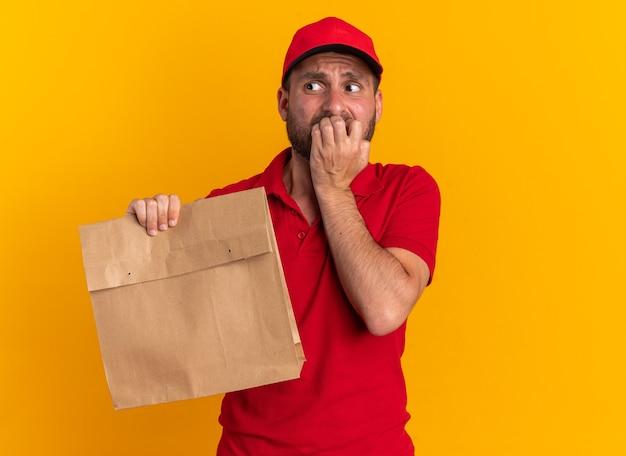 Niespokojny młody kaukaski dostawca w czerwonym mundurze i czapce, trzymający papierowy pakiet, trzymający palce na wardze, patrząc na bok