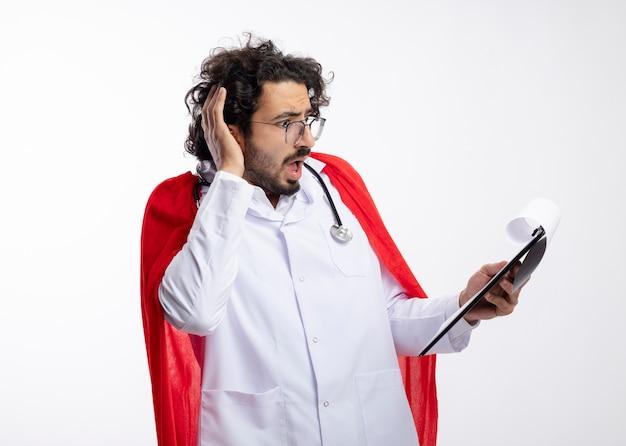 Niespokojny młody kaukaski mężczyzna superbohatera w okularach optycznych w mundurze lekarza z czerwonym płaszczem i stetoskopem na szyi kładzie rękę na głowie i patrzy na schowek z miejscem na kopię