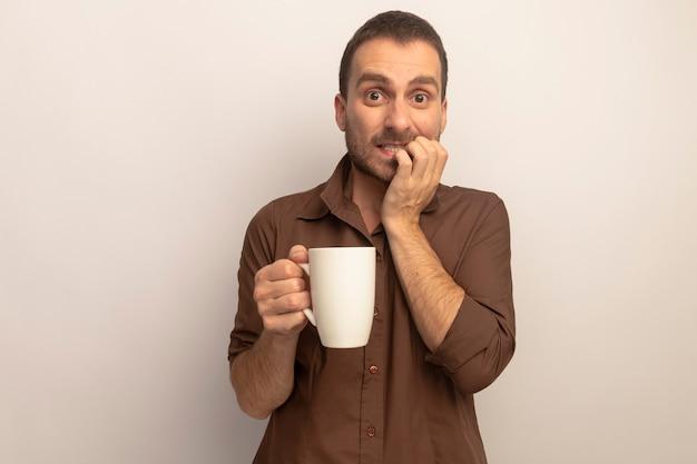 Niespokojny młody kaukaski mężczyzna trzyma filiżankę herbaty kładąc dłoń na wardze patrząc na kamery na białym tle na białym tle z miejsca kopiowania