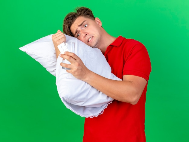 Niespokojny młody przystojny blondyn chory trzymający poduszkę, kładąc na niej głowę, trzymając i patrząc na szklankę wody i tabletki medyczne odizolowane na zielonej ścianie