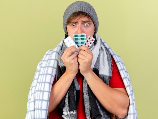 Niespokojny młody przystojny blondyn chory w czapce zimowej i szaliku owiniętym w kratę dotykając ust z paczkami tabletek medycznych patrząc w dół odizolowany na oliwkowej ścianie