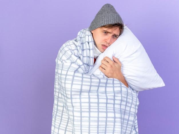 Niespokojny młody przystojny blondyn chory w czapce zimowej owinięty w kratę trzyma poduszkę kładąc głowę na niej, patrząc prosto na fioletowym tle z miejsca na kopię
