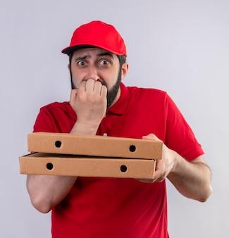 Niespokojny młody przystojny kaukaski mężczyzna dostawy ubrany w czerwony mundur i czapkę, trzymając pudełka po pizzy i kładąc rękę na ustach na białym tle