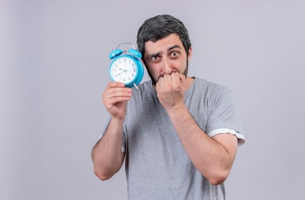 Niespokojny młody przystojny kaukaski mężczyzna trzyma budzik i gryzie palce na białym tle na biały z miejsca na kopię