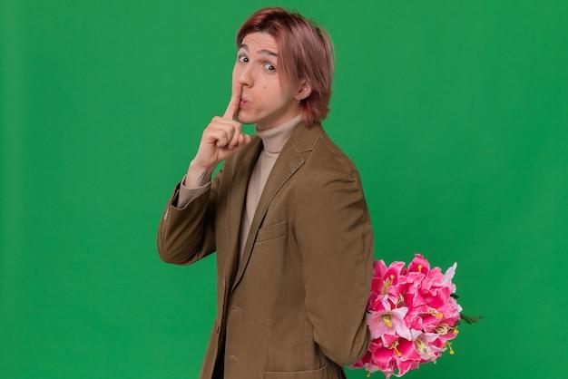 Niespokojny młody przystojny mężczyzna trzyma bukiet kwiatów za plecami i robi gest ciszy