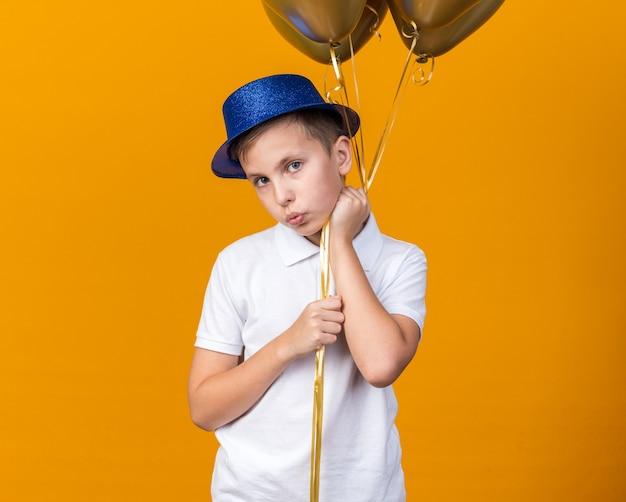 Niespokojny młody słowiański chłopiec w niebieskim kapeluszu imprezowym trzymający balony z helem odizolowane na pomarańczowej ścianie z miejscem na kopię