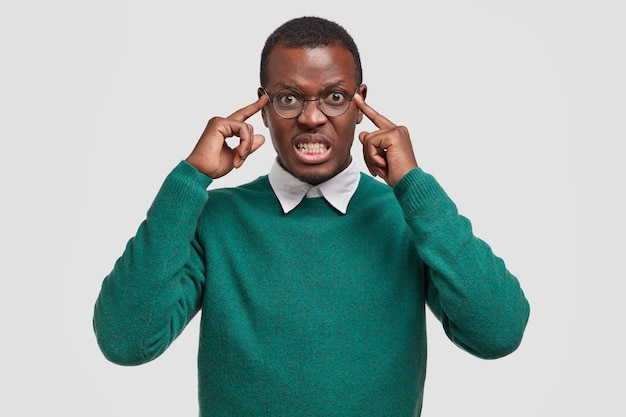 Niespokojny, niezadowolony, zaniepokojony afroamerykanin dorosły mężczyzna trzyma palce na skroniach, próbuje się skoncentrować, ma straszny ból głowy, zaciska zęby