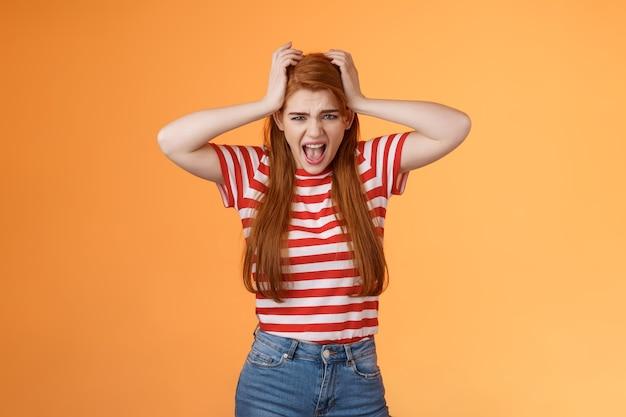 Niespokojny przygnębiony znudzony wkurzona ruda dziewczyna krzycze zdenerwowany chwyć za głowę ciągnij włosy krzycząc przeszkadza ...