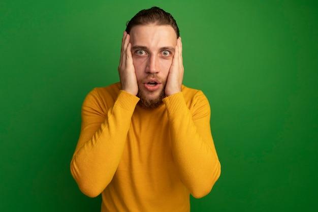 Niespokojny przystojny blondyn kładzie ręce na twarzy na zielono