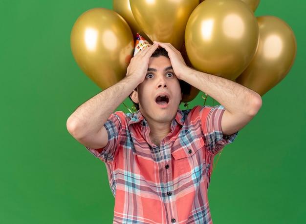 Niespokojny przystojny kaukaski mężczyzna w urodzinowej czapce kładzie ręce na głowie stojąc przed balonami z helem
