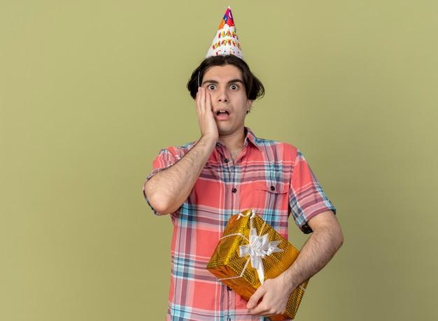 Niespokojny przystojny kaukaski mężczyzna w urodzinowej czapce kładzie rękę na twarzy i trzyma pudełko na prezent