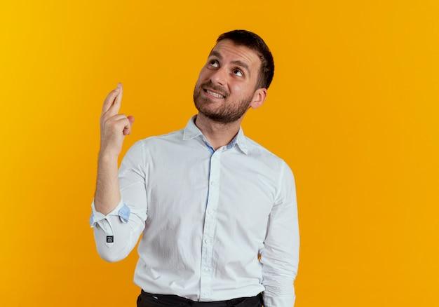 Niespokojny przystojny mężczyzna krzyżuje palce patrząc na białym tle na pomarańczowej ścianie