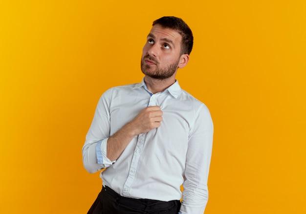 Niespokojny przystojny mężczyzna patrzy na białym tle na pomarańczowej ścianie