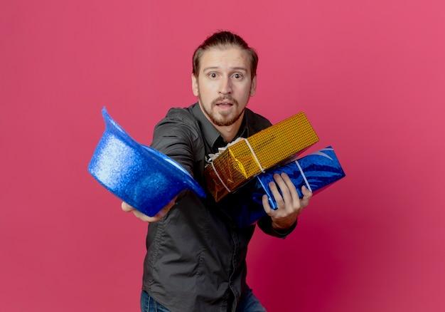 Niespokojny przystojny mężczyzna stoi bokiem, trzymając pudełka z prezentami i niebieski kapelusz na różowej ścianie