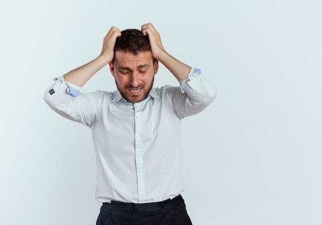 Niespokojny przystojny mężczyzna trzyma głowę na białym tle na białej ścianie