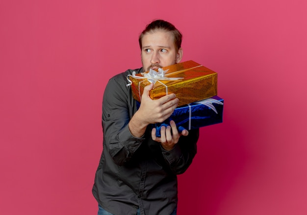 Niespokojny przystojny mężczyzna trzyma pudełka na prezenty patrząc z boku na białym tle na różowej ścianie