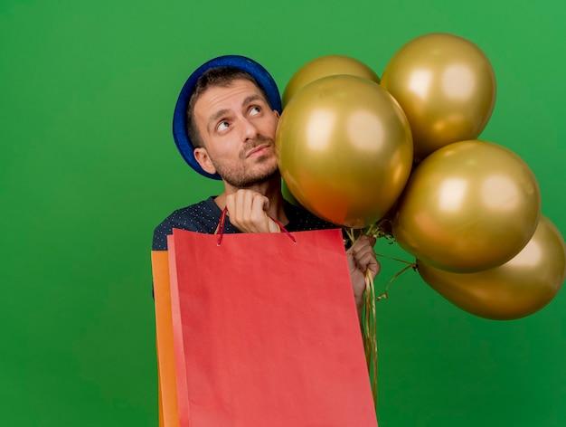 Niespokojny przystojny mężczyzna ubrany w niebieski kapelusz partii trzyma balony z helem i papierowe torby na zakupy patrząc w górę na białym tle na zielonej ścianie