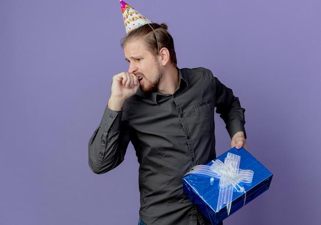 Niespokojny przystojny mężczyzna w czapce urodzinowej trzyma pudełko, patrząc z boku na białym tle na fioletowej ścianie