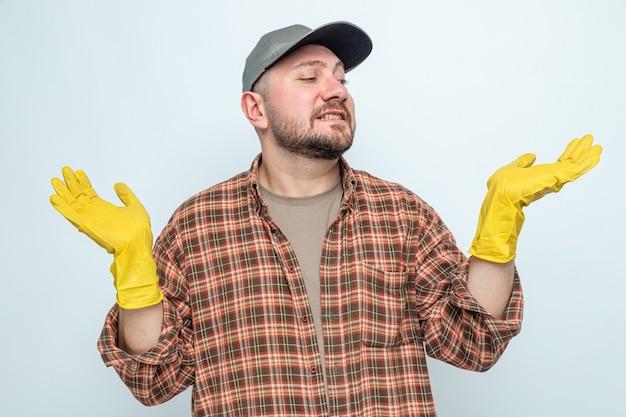 Niespokojny słowiański sprzątacz w gumowych rękawiczkach, trzymający otwarte ręce i patrzący na bok