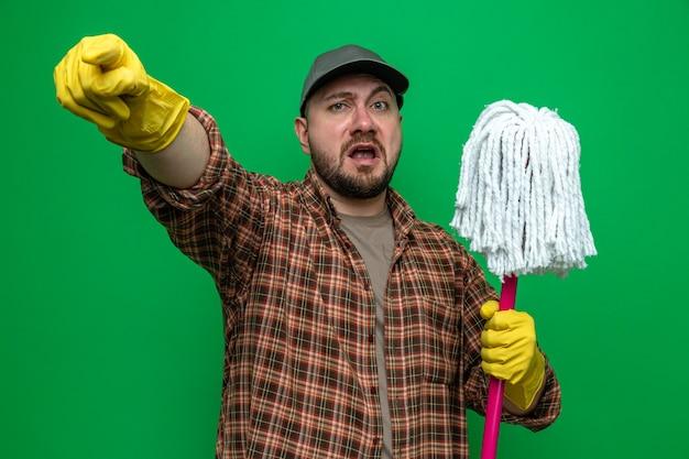 Niespokojny sprzątacz w gumowych rękawiczkach, trzymający tłum i wskazujący na bok