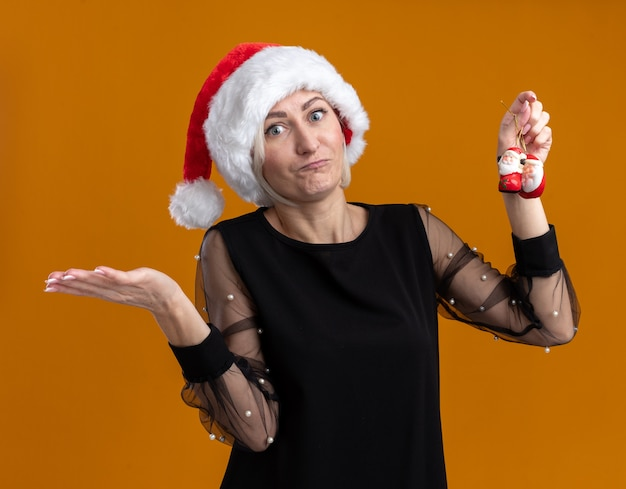 Nieświadoma blondynka w średnim wieku ubrana w świąteczny kapelusz trzymający świętego mikołaja ozdoby świąteczne pokazujące pustą dłoń na pomarańczowej ścianie