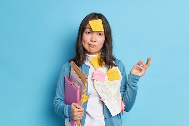 Nieświadoma etniczna kobieta wzrusza ramionami ma wątpliwości, że prace na papierze dyplomowym próbują nauczyć się matematycznych formuł, a grafika trzyma teczki.