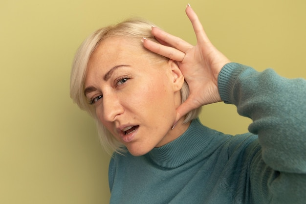 Nieświadoma ładna blondynka słowiańska kobieta trzyma rękę za ucho na białym tle na oliwkowej ścianie