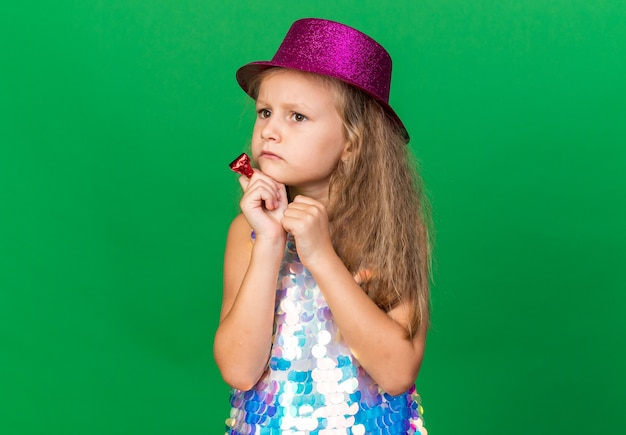 Nieświadoma mała blondynka w fioletowym kapeluszu imprezowym trzymająca gwizdek i patrząca na bok odizolowaną na zielonej ścianie z miejscem na kopię