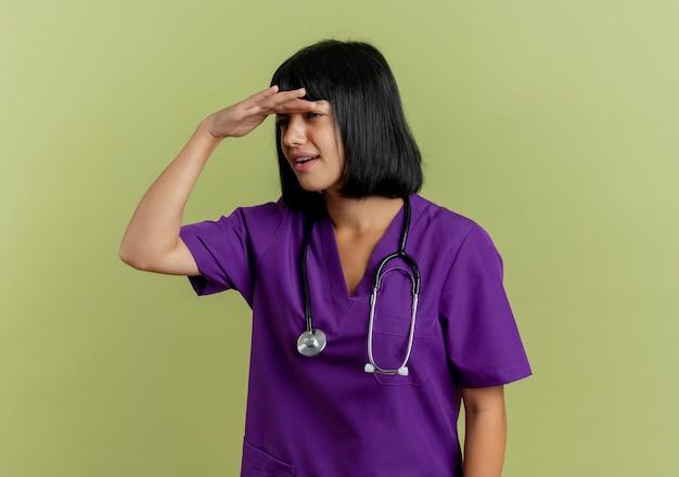 Nieświadoma młoda brunetka lekarka w mundurze ze stetoskopem trzyma dłoń na czole, próbując zobaczyć, patrząc z boku na tle oliwkowo-zielonym z miejscem na kopię