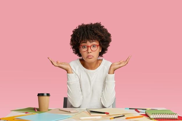 Nieświadoma młoda kobieta ma fryzurę afro, wzrusza ramionami ze zdumieniem i zwątpieniem, nosi przezroczyste okulary, siedzi przy biurku