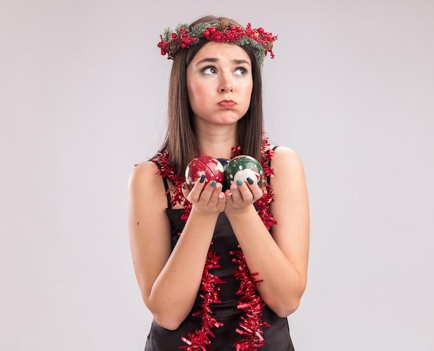 Nieświadoma młoda, ładna dziewczyna kaukaska ubrana w świąteczny wieniec na głowę i świecącą girlandę na szyi, trzymając bombki