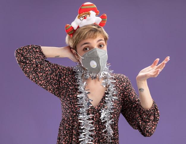Nieświadoma młoda ładna dziewczyna nosząca opaskę na głowę świętego mikołaja i błyszczącą girlandę na szyi z maską ochronną pokazującą pustą rękę trzymającą kolejną za głową odizolowaną na fioletowej ścianie