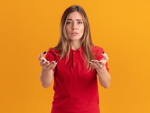 Nieświadoma młoda ładna kobieta wskazuje z przodu rękami odizolowanymi na pomarańczowej ścianie