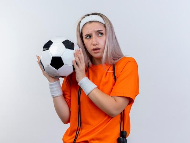 Nieświadoma młoda sportowa kobieta z szelkami i skakanką na szyi z opaską na głowę i opaskami na nadgarstki trzyma piłkę patrząc z boku na białym tle na białej ścianie