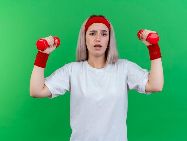 Nieświadoma młoda sportowa kobieta z szelkami na sobie opaskę i opaski na rękę trzyma hantle na białym tle na zielonej ścianie