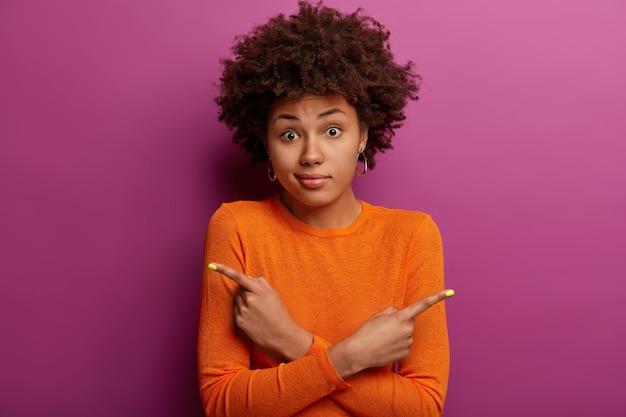 Nieświadoma niezdecydowana kobieta z kręconymi fryzurami krzyżuje ręce na piersi