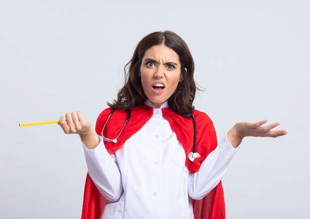 Nieświadoma superwoman w mundurze lekarza z czerwoną peleryną i stetoskopem trzyma rękę otwartą i trzyma ołówek na białej ścianie