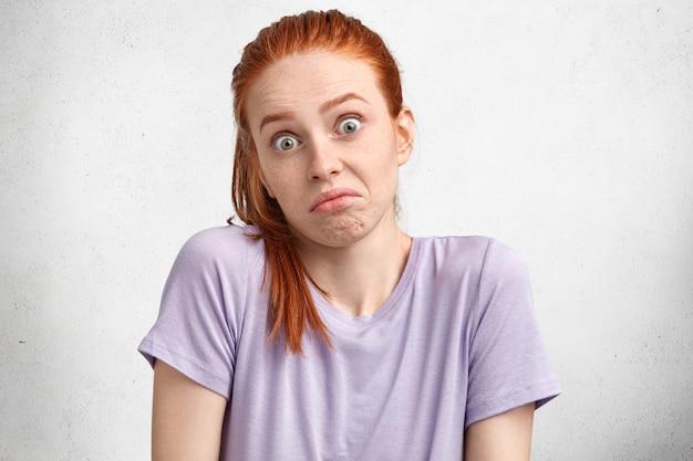 Nieświadoma, urocza rudowłosa suczka z niepewnym wyrazem twarzy, niepewna i zdziwiona, gdy podejmuje ważną decyzję, wpatruje się w kamerę z zakłopotaniem