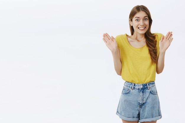 Nieświadoma uśmiechnięta śliczna dziewczyna przeprasza i pokazuje podniesione puste ręce