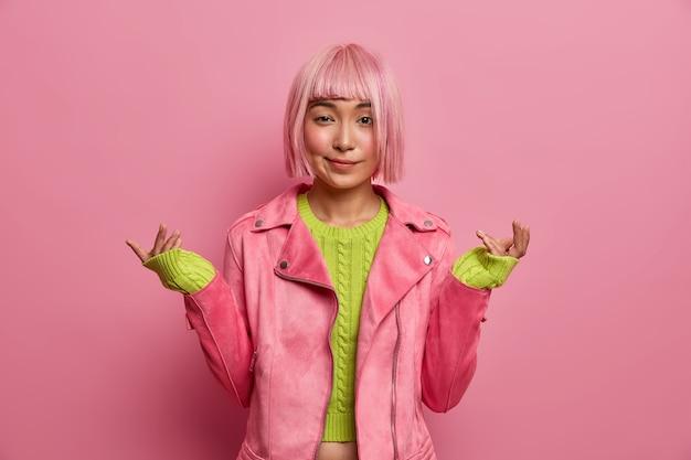 Nieświadoma wahająca się kobieta z różową fryzurą boba unosi ręce w oszołomieniu, nie ma pojęcia, co się dzieje