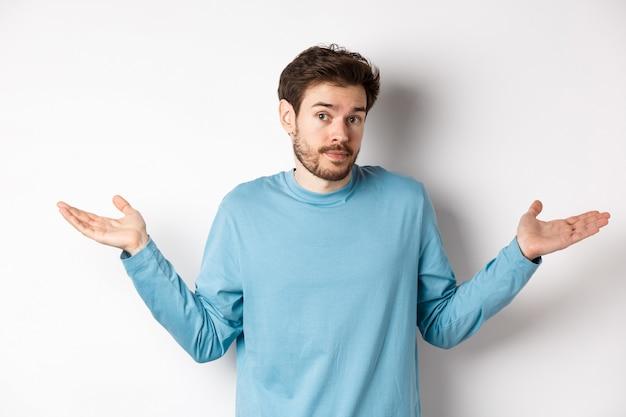 Nieświadomy brodaty facet w niebieskiej koszuli, wzruszający ramionami i nieświadomy patrzenia w kamerę, nic nie wie, stojący na białym tle