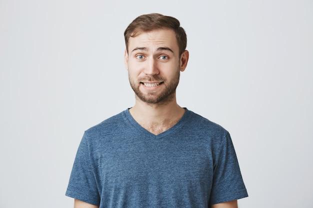 Nieświadomy brodaty mężczyzna uśmiecha się niezręcznie